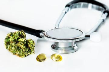 Medizinische Cannabis Ölkapseln mit Knospe und Stethoskop