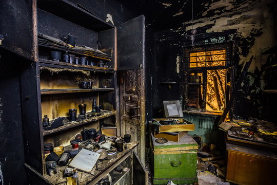 Burnt house interior. Burned kitchen, furniture, door, charred walls and ceiling in black soot