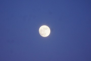 Full moon shining in the bright blue sky