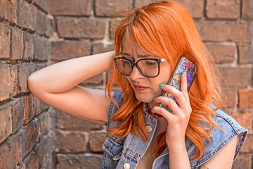 Beautiful disappointed redhead Caucasian girl talking on smart phone