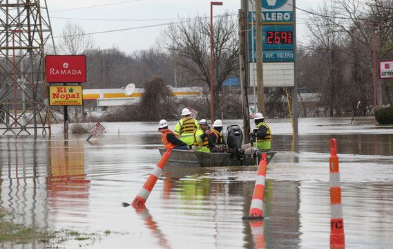 Employees of Louisville Gas & Electric make their way to turn off power to companies along the Ohio River, after it flooded in Louisville