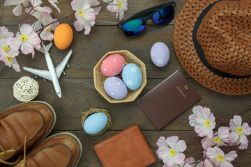 Table top view shot of decoration Happy Easter holiday background concept.Flat lay essential objects plan to travel vacation on modern brown wooden at office desk. Accessory for traveler to trip.
