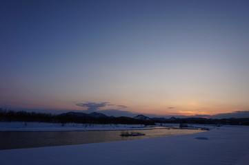冬の夕暮れ 川 日没 雪景色 太陽