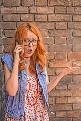 Beautiful angry and confused redhead Caucasian girl talking on smart phone