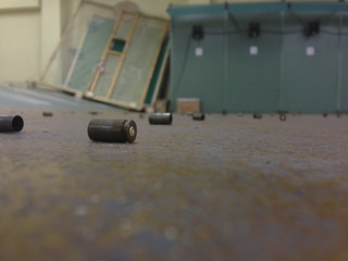 Used pistol casings on concrete floor in a warehouse.