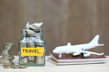 Saving planning for Travel budget of holiday concept,Financial,Stack of coins money in the glass bottle and airplane on passport with wooden background