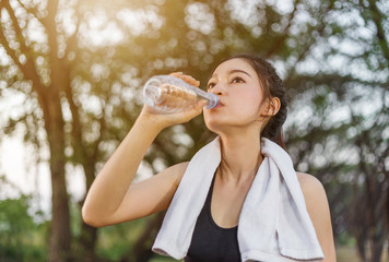 young sporty woman drinking water in park