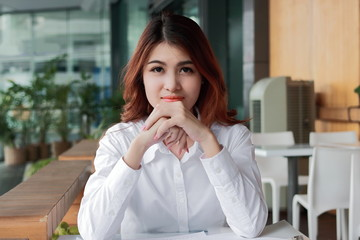 Portrait of confident young Asian businesswoman looking on camera at workspace in office background. Leadership woman concept.