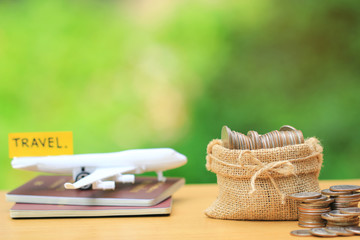 Saving planning for Travel budget of holiday concept,Financial,Stack of coins money in bag and airplane on passport with natural green background