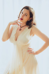 Young woman in retro pin up style and white dress poses against a white curtain backdrop