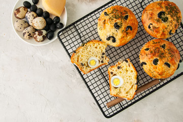 Savory muffins with olives and herbs on a wire rack on a white stone backdrop.