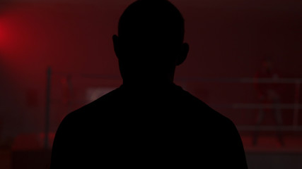 Silhouette of a man who comes into the room with a red light, back view. Shadow of man in the red room. Silhouette of a man in the light