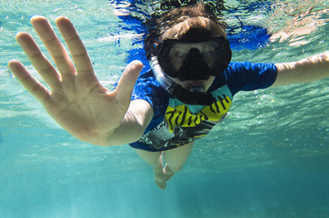 Teenager in a mask and a tube under the water