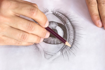 Drawing eye with pencil. Close up hands with pencil drawing human eye