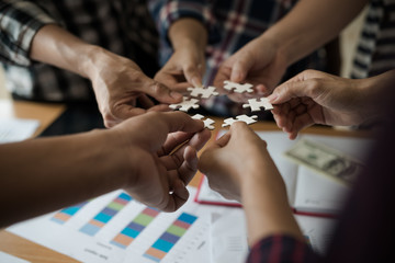 Hands group of business people assembling jigsaw puzzle white. Below is the graph paper business documents placed on a wooden table in the meeting room.