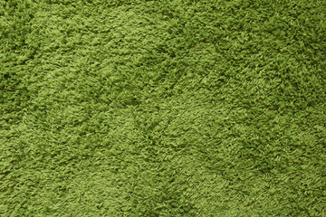 Green carpet. Surface imitating green grass. A close-up photograph. Top view