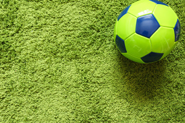 Football (Soccer) ball on a green surface imitating artificial grass. Sports photography