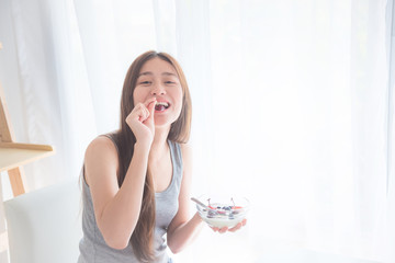 Beautiful young asian woman eating yogurt with berries for breakfast in the morning