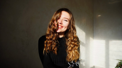 Female Smiling, Looking at Camera, Laughs or Flirts. Girl With Long Curly Brown Hair Sitting in White Room With Christmas Lights and New Year Chloe on Background. Scene Filmed by Sun at Xmas Time.