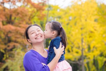 Little asian girl kissing her mother in autumn park