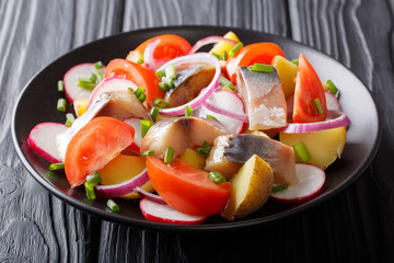 Fish salad: smoked mackerel with potatoes, radish, onions and tomatoes close-up on a plate on a table. horizontal