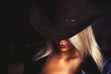 Portrait of a beautiful bright blond haired girl with caountry hat