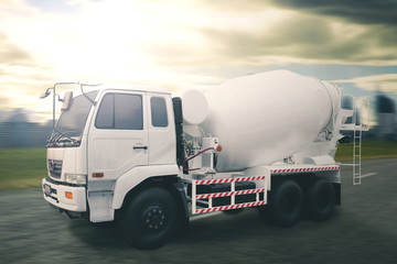 White concrete mixer truck with dramatic sky