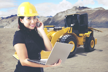 Young female architect working with laptop while making a phone call in front of an excavator on a construction site