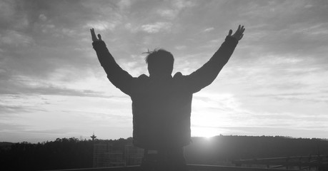 Praise and worship concept: Silhouette human raising hands to praying God on blurred cross with crown of throne sunset background