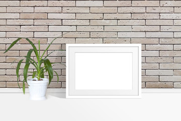 Blank photo frame mock up and yucca plant in flower pot near bricks wall, interior decoration accessory