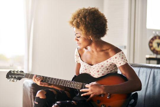 african american woman playing guitar at home