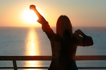 Silhouette of a Girl Waking up Stretching Arms in Morning Sunrise Light