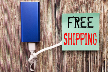 Handwritten text caption showing Free Shipping. Business concept writing for Delivery For Transport written on sticky note with copy space old wood wooden background with power bank