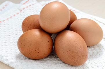 Brown chicken eggs on napkin.