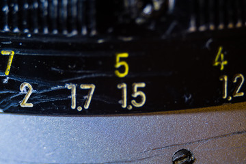 Old manual control lens body. Scratches and dirt. Close-up on the numbers of aperture ring