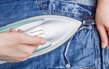 Photo of a man ironing jeans,