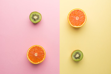 Creative Concept. Two Half Orange and Two Half Kiwi on Geometry Yellow Pink Pastel Background, Top...