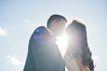Kissing loving wedding couple on sunlight.