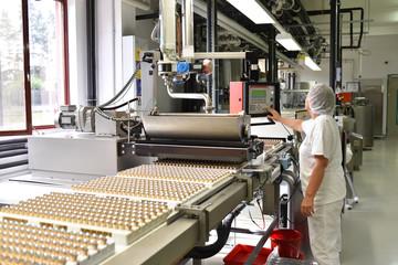 Arbeiterin an einer Produktionslinie für Süssigkeiten bedient eine Maschine in der Lebensmittelindustrie // Worker on a production line for sweets operates a machine in the food industry