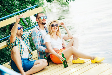 Group of friends two men and woman in sunglasses spending time on nature sitting on bridge above river drinking beer and have fun! Barbecue Summer People Emotions Lifestyle Fashion concepts