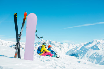 Photo of snowboard, skis on background of sitting sports couple on snowy hill