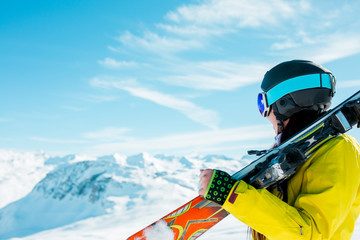 Side view of sporty woman in helmet with skis on her shoulder against background of winter hills