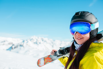 Portrait of sporty woman in helmet with skis on her shoulder against background of winter hills
