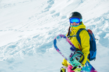 Picture of smiling girl in helmet and with snowboard against background of snowy landscape