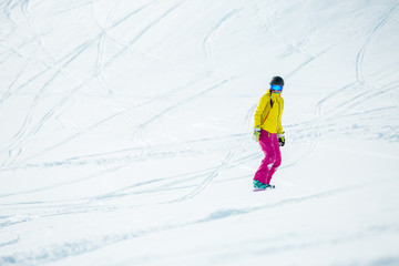 Photo of woman wearing helmet in sports clothes snowboarding