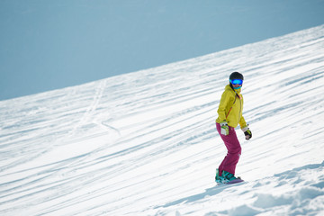 Image of sports woman in helmet and mask, snowboarding from mountain slope