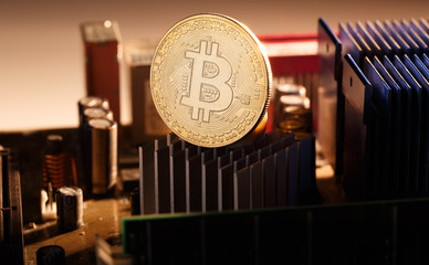 Picture of bitcoin and processor on orange background