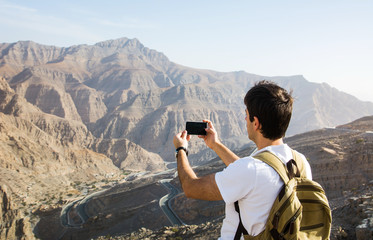 Man taking picture of the mountain range view