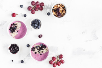 Breakfast with muesli, acai blueberry smoothie, fruits on white background. Healthy food concept. Flat lay, top view, copy space
