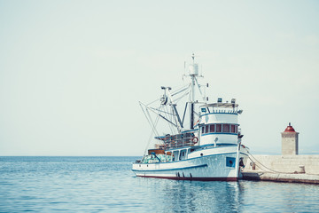 Fishing trawler in the beautiful harbor of a small town Postira - Croatia, island Brac